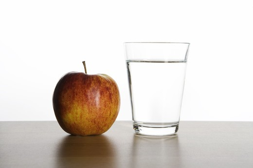 An apple and a glass of water. : Stock Photo