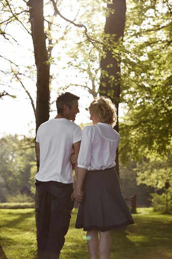 Stock Photo: 4306R-18246 Couple walking in a forest, Copenhagen, Denmark.