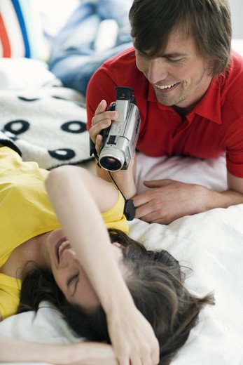 Stock Photo: 4306R-18356 A young couple with a video camera.