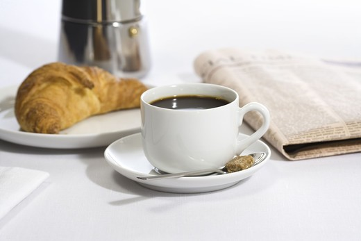Cup of coffee, a newspaper and a Danish pastry, Sweden. : Stock Photo