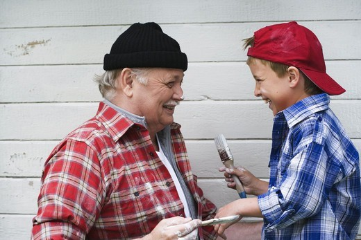 Stock Photo: 4306R-18624 Grandfather and grandson painting their summer cottage, Sweden.