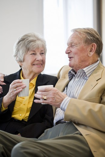 An old couple holding cups of coffee, Sweden. : Stock Photo