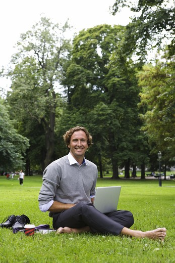 Stock Photo: 4306R-19895 A man with a laptop in a park, Sweden.