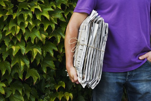 Stock Photo: 4306R-19914 A man holding newspapers for recycling.