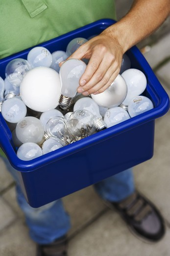 Stock Photo: 4306R-19921 A man holding light bulbs for recycling.