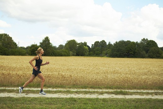 Stock Photo: 4306R-20032 Woman jogging in an open landscape, Sweden.