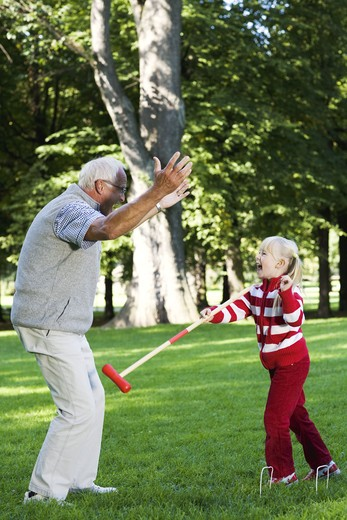 Girl and senior man playing croquet in the park, Sweden. : Stock Photo