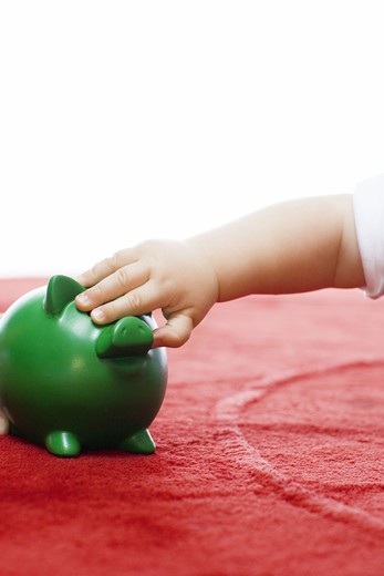 Stock Photo: 4306R-20425 A baby with a piggy bank.