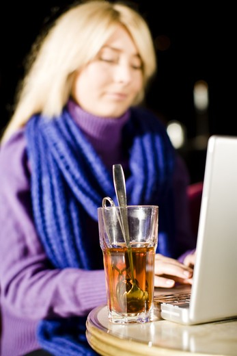 Young woman sitting in a cafe using a laptop, Sweden. : Stock Photo