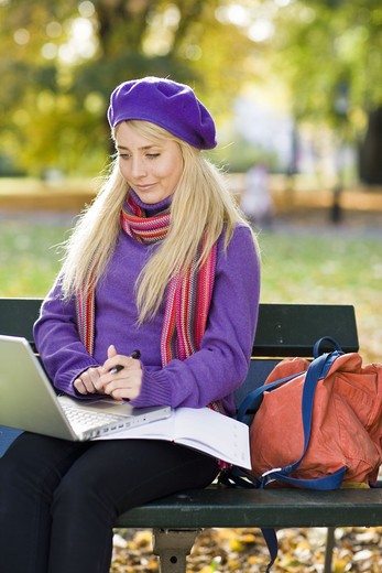 Stock Photo: 4306R-20887 A woman sitting on bench in a park using a laptop, Stockholm, Sweden.