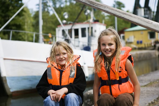 Girls sitting next to a lock chamber, Vastergotland, Sweden. : Stock Photo
