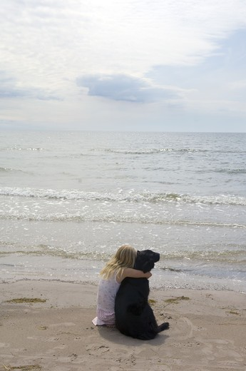 Girl with dog sitting on beach : Stock Photo