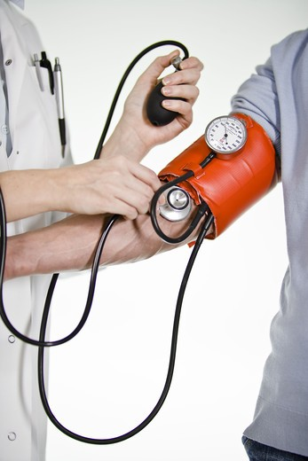 A female doctor using a blood-pressure gauge, Sweden. : Stock Photo