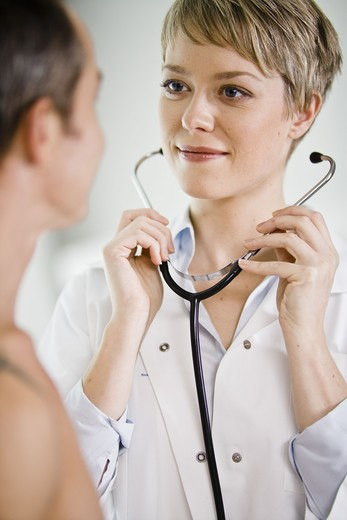 Stock Photo: 4306R-21704 A doctor using a stethoscope at a patient, Sweden.