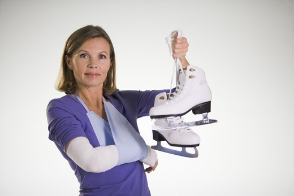 An injured woman holding skates. : Stock Photo