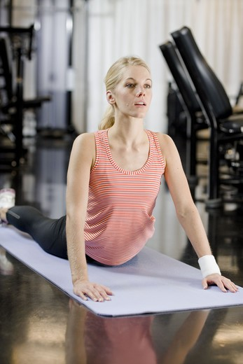 A woman doing stretching exercises at a gym, Sweden. : Stock Photo