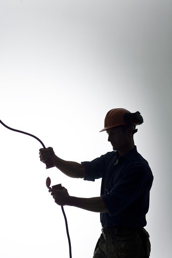 Stock Photo: 4306R-22072 A construction worker with an electric cable.