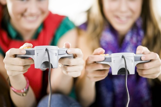 Stock Photo: 4306R-22148 Two teenage girls playing a video game.