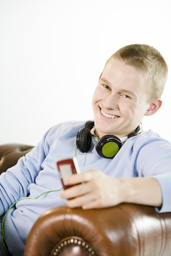 Stock Photo: 4306R-22178 A teenage boy sitting in an armchair using a mobile phone.
