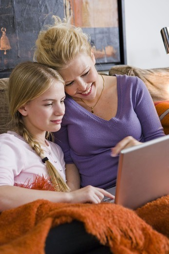 Mother and daughter using a laptop in a couch, Sweden. : Stock Photo
