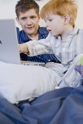A father and son using a laptop in bed, Sweden. : Stock Photo