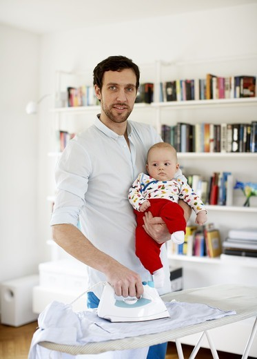 Stock Photo: 4306R-23308 Father holding baby and ironing