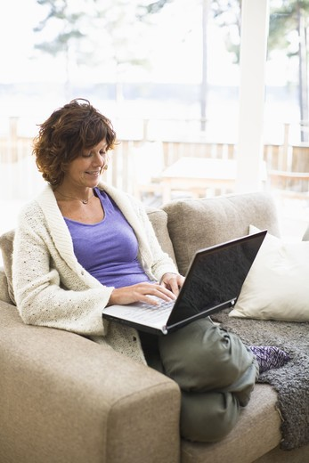 Stock Photo: 4306R-23664 Woman sitting on sofa and surfing internet