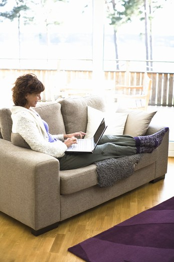 Stock Photo: 4306R-23665 Woman sitting on sofa and surfing internet