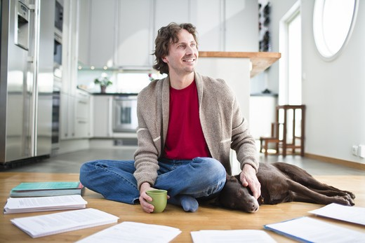 Mid-adult man doing paperwork on floor, while dog is sleeping next to him : Stock Photo