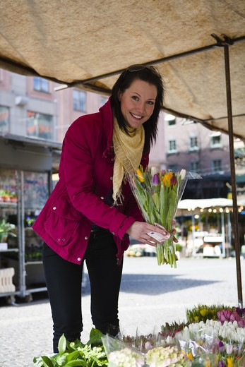 Young woman paying for bunch of flowers at market stall : Stock Photo