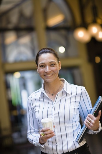 Stock Photo: 4306R-23876 Portrait of businesswoman holding takeaway coffee in one hand and laptop in another