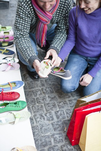Couple observing shoes at outdoor market stall : Stock Photo