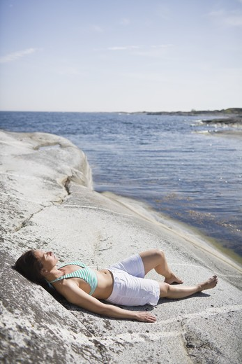 Stock Photo: 4306R-24028 Woman lying on rock