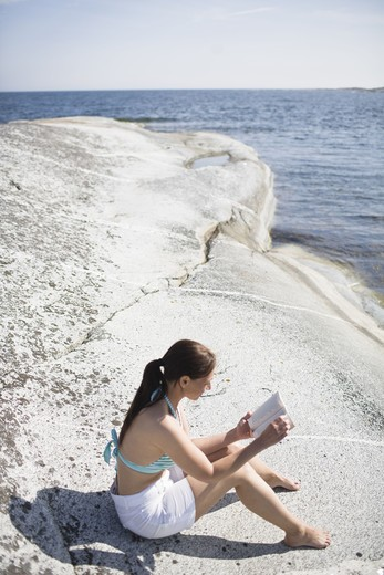 Stock Photo: 4306R-24036 Woman sitting on rock and reading book
