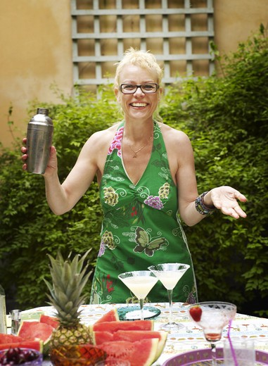 Woman mixing cocktail, smiling : Stock Photo