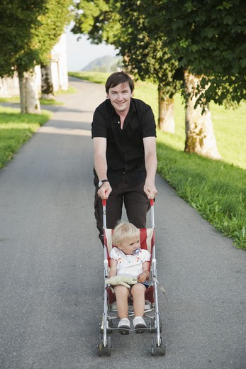 Father carrying daughter in pushchair at park : Stock Photo