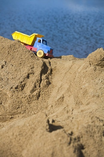 Toy truck on top of heap of sand : Stock Photo