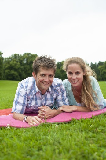 Mid adult couple lying on blanket and looking at camera : Stock Photo