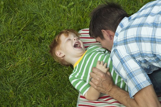 Stock Photo: 4306R-24740 Mid adult father playing with son