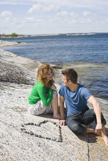 Mid adult couple sitting on beach near heart made from pebbles : Stock Photo