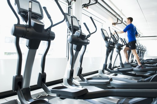 Man running on exercise machine in gym : Stock Photo