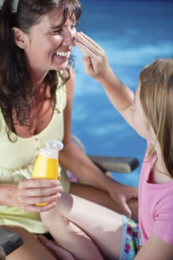 Stock Photo: 4306R-25102 Girl applying suntan lotion on her mothers nose