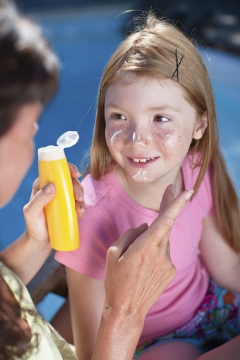 Mother applying suntan lotion on her daughters face : Stock Photo