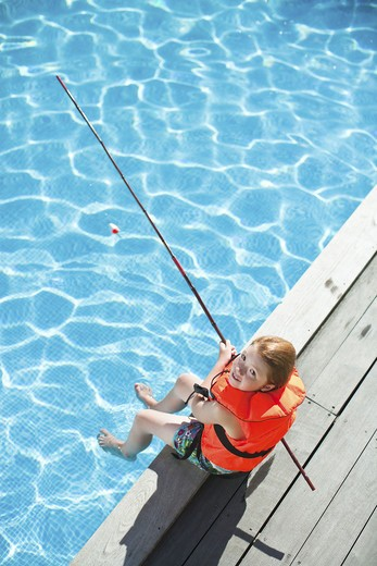 Stock Photo: 4306R-25143 Girl fishing in swimming pool