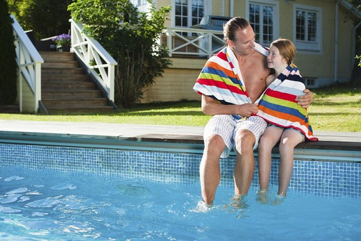 Stock Photo: 4306R-25150 Father and daughter sitting at the edge of swimming pool