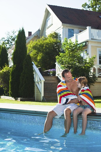 Father and daughter sitting at the edge of swimming pool : Stock Photo