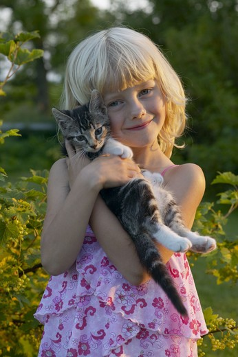 Stock Photo: 4306R-25442 Portrait of girl embracing cat outdoors