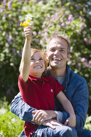 Stock Photo: 4306R-25595 Father and son with flowers, in bright sunlight