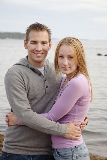 Portrait of young couple embracing by sea : Stock Photo
