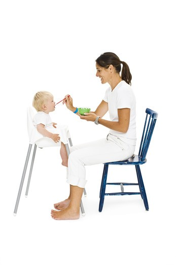 Boy in high chair being fed by mother : Stock Photo